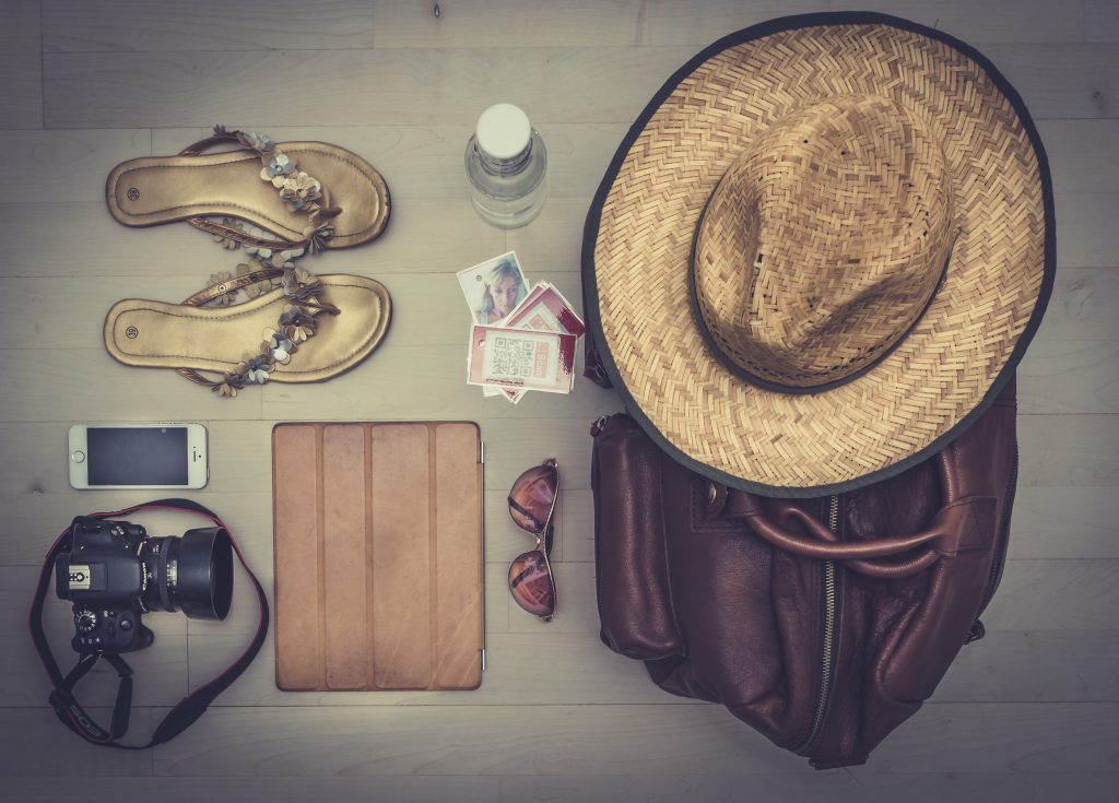 flat lay of things to pack for south america - camera, hat, sandals, diary