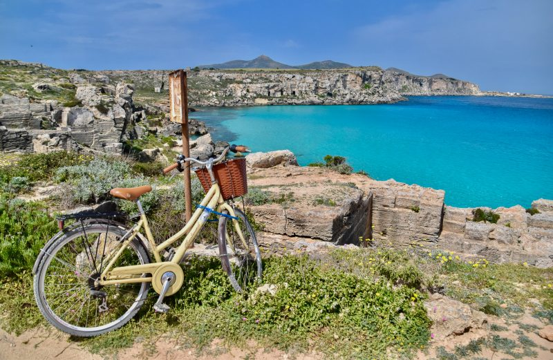 calla rossa favignana sicily - bike propped up against some rocks with a bright blue ocean behind