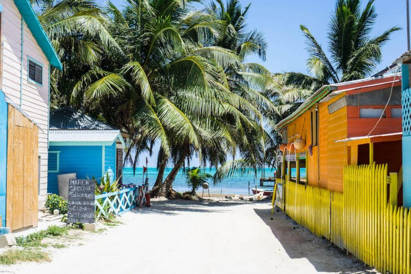 sunny winter holidays in Belize - colourful huts, palm trees and sandy streets.