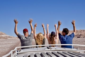 G adventures vs Intrepid - tour companies reviewed. 4 people enjoying themselves on the roof seats of a tour truck.