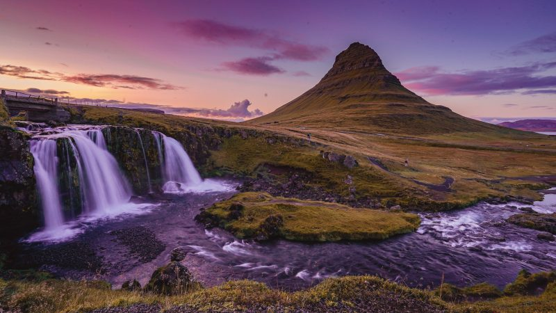 Sunset at Kirkjufellsfoss on the snaefellness peninsula in icleand. a conical mountain sits behind 2 small waterfalls and the sky is a blend of purple, yellow and pink tones.