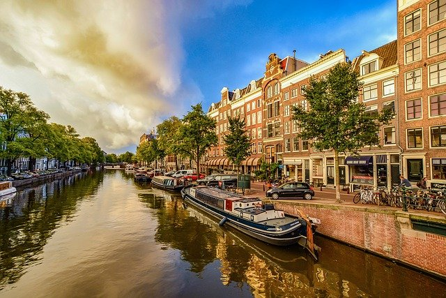 best city breaks for couples amsterdam canals with canal boats in the sunshine
