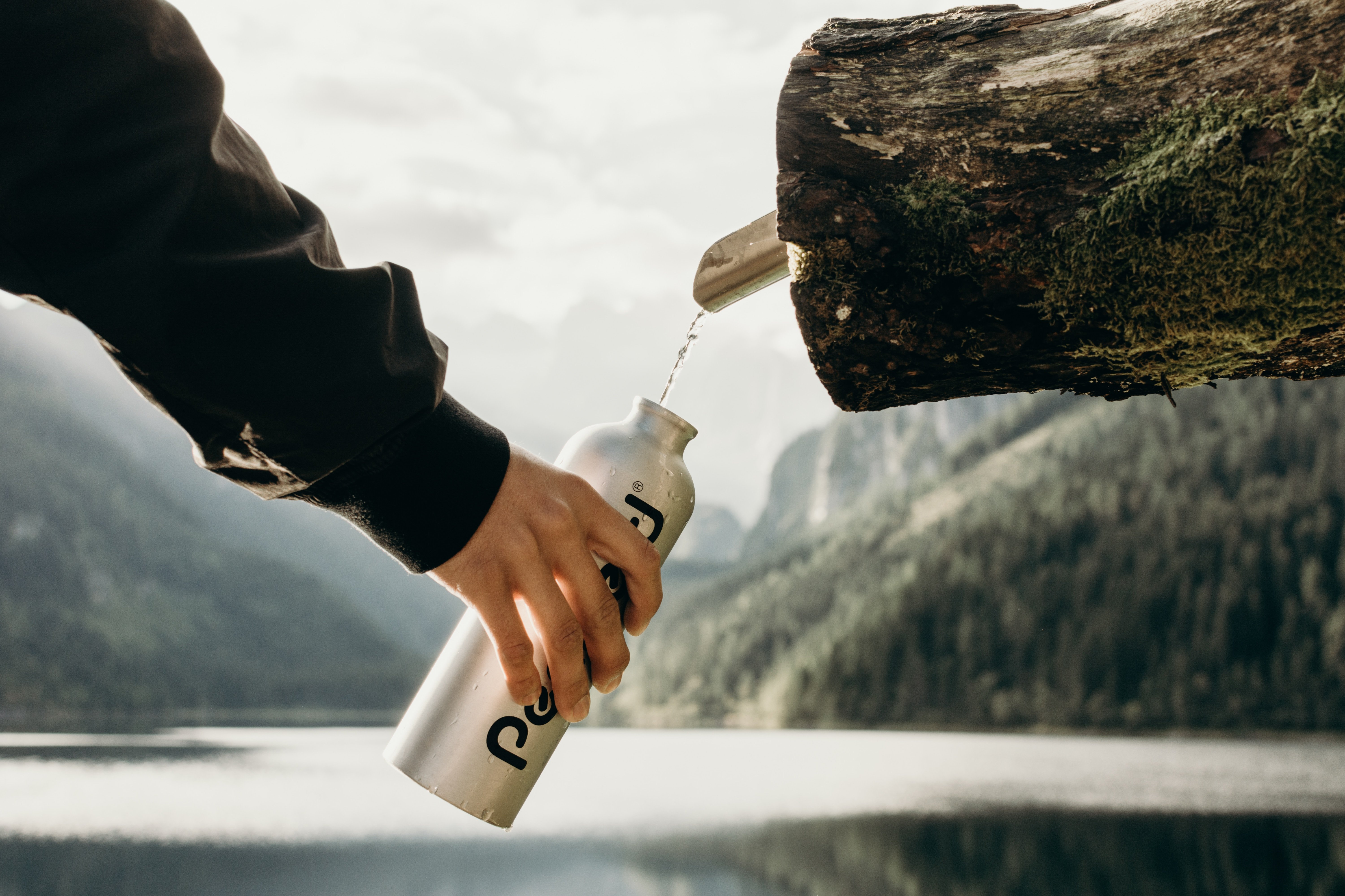 the best water bottle with filter for travel - filling up from a natural stream