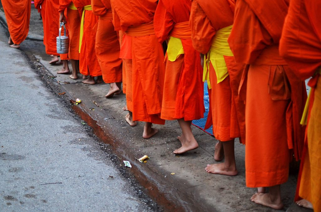 backpacking laos giving alms to monks - monks feet