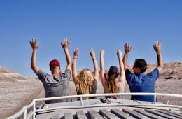 best group travel for singles 4 people riding on the roof of a truck with arms in the air