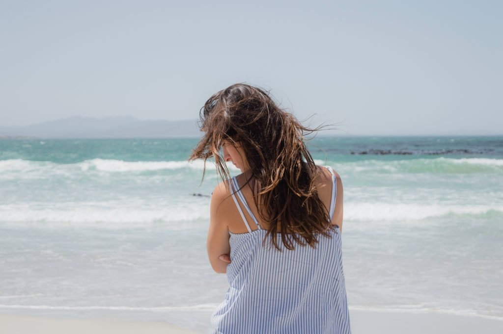 travelling with back pain - women sad on beach