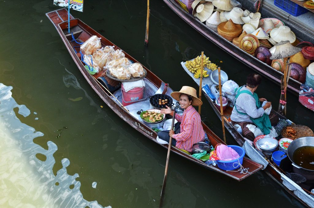 make sure a floating market day trip is on your thailand itinerary - lady looking up from her boat