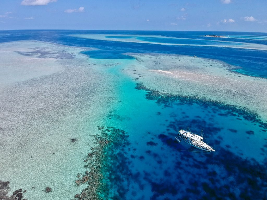 drone photo of the maldives and the dhoni cruise boat