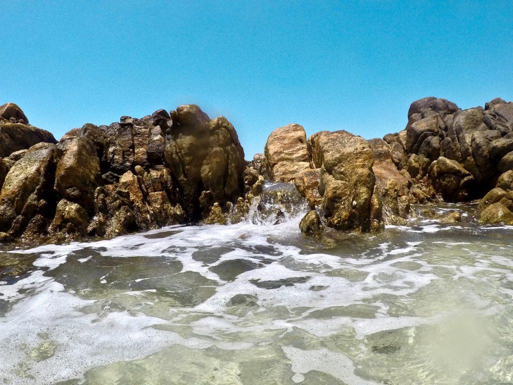 the wall of rocks creating a lagoon at secret beach