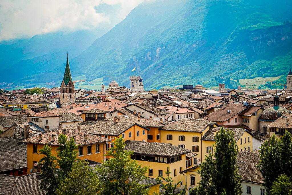 View of Trento with the mountains in the background and a church steeple towering over the houses, the perfect base for a weekend in Trentino
