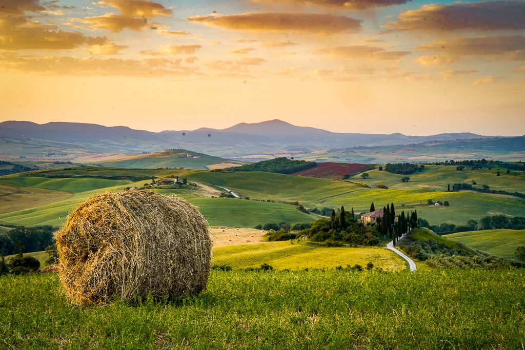 countryside view of tuscany rolling hills and hay bales - one of the scenes you'll see often on this 5 day tuscany itinerary