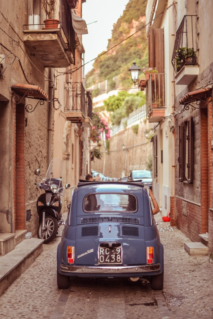 blue car in a narrow italy alley