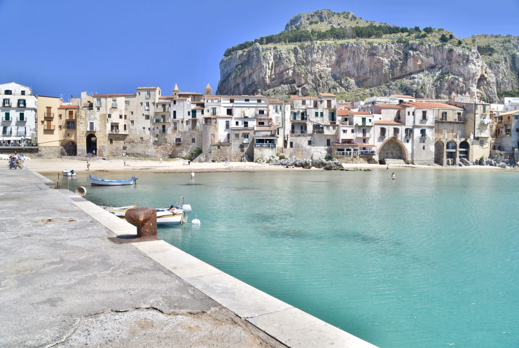 jetty leading to cefalu town with bright aqua ocean