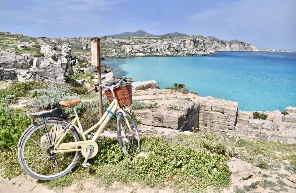 bike propped against a wall overlooking perfect ocean at favignana sicily italy