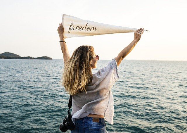 person travelling with epilepsy holding a flag saying freedom