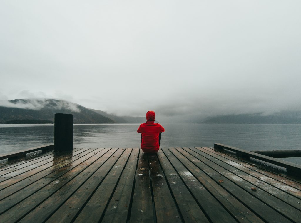 man sat on a jetty on a bleak day suffering with travel depression