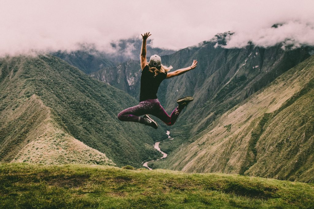 girl jumping in air on a mountain finally free of the traveller's blues
