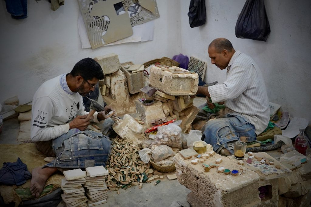 people working to make mosaics for pots in fes, morocco