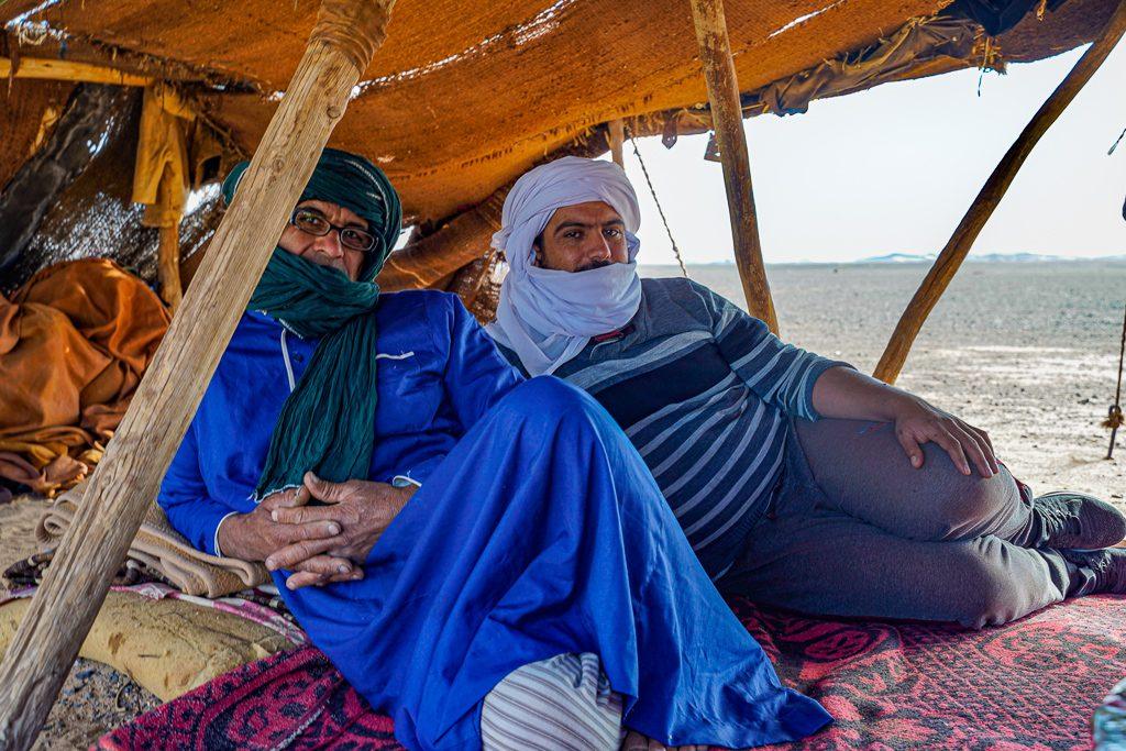 2 berber men relaxing in a tent in the desert