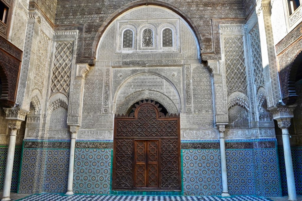 beautiful architecture in Fes at medersa with tiny green mosaic patterns on the walls