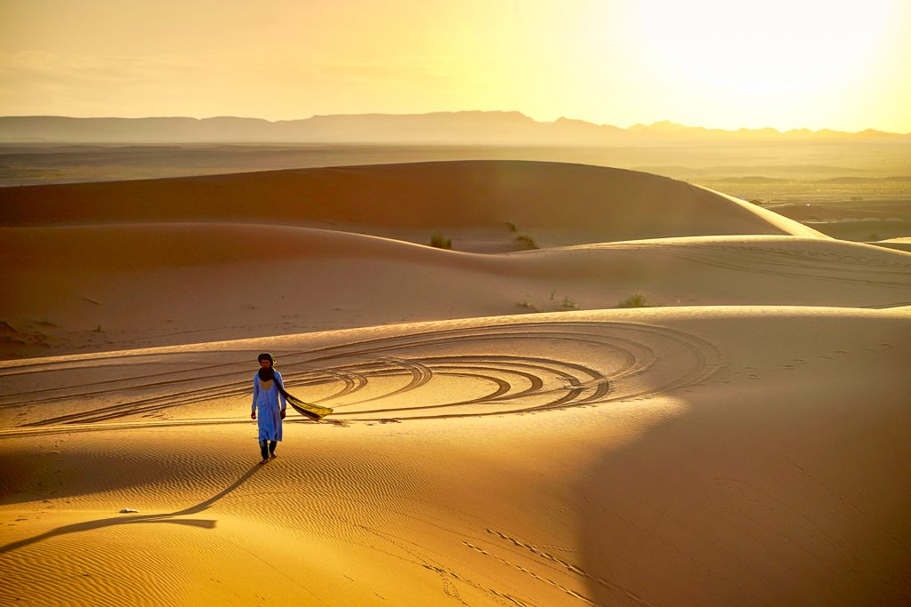 picture of a man walking acoss the sand dunes at sunset