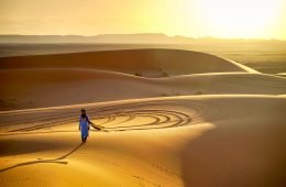 picture of a man walking acoss the sand dunes at sunset on . a desert trip in Morocco
