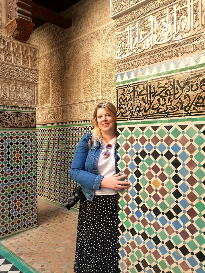 me dressed in a long skirt standing next to a pillar in mosaics