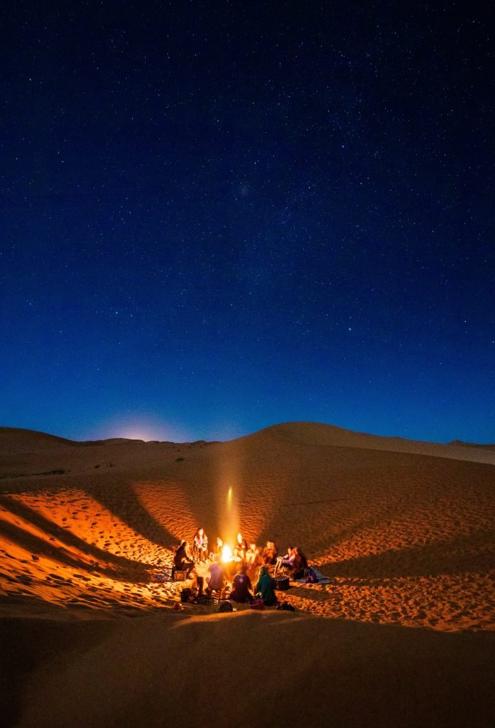 planning a desert safari from marrakech - group huddled around a campfire on the dunes