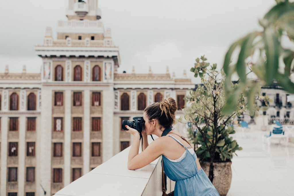 girl using best backpacking camera leaning over a bridge to take a photo