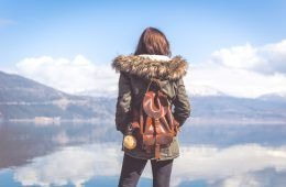 girl in winter looking onto a lake wearing a theft proof travel bag