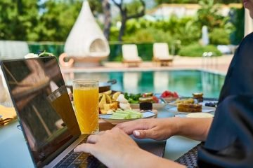 travel bloggers working on laptop by the pool