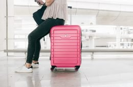 long haul flight essentials - girl sitting on pink suitcase