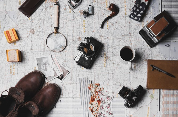 travel flat lay with map , camera, boots etc - travel hacks to save money