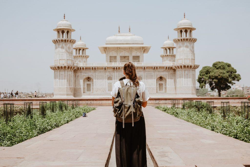girl with a backpack walking towards taj mahal