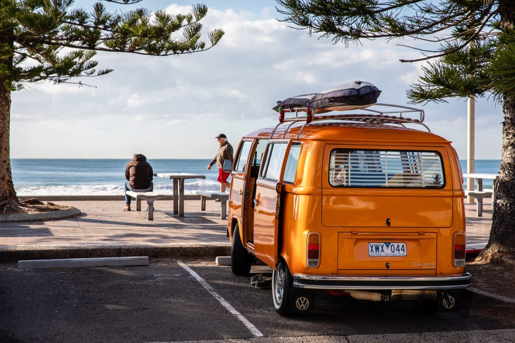 orange campervan parked by a beach on a road trip