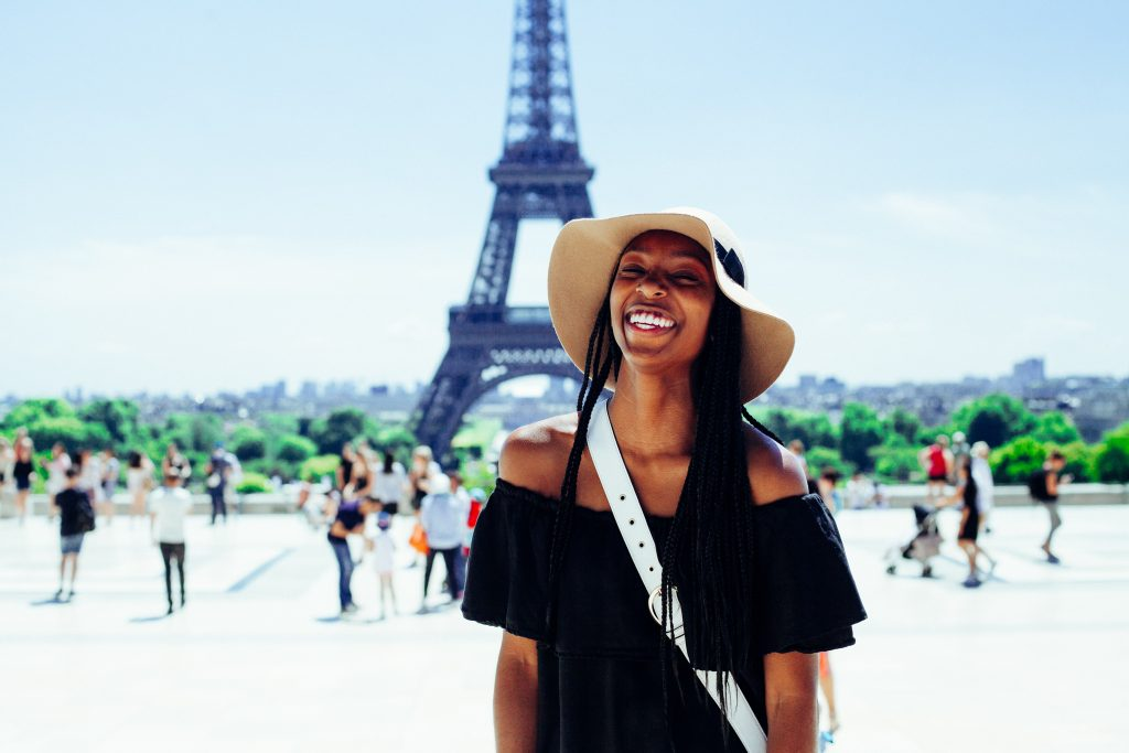 girl stood in front of the eiffel tower on a sunny day